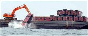 Crane dropping railroad car from cargo ship